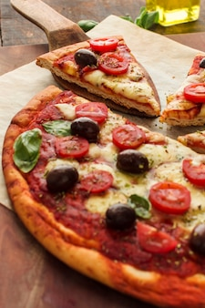 Rebanada de pizza deliciosa en espátula de madera
