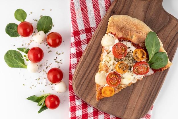Rebanada de pizza deliciosa en tablero de madera