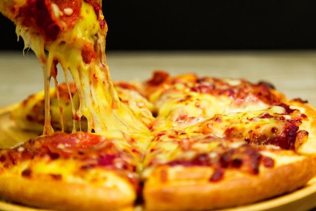 Rebanada de pizza muy cursi en la mano. rebanada de pizza con queso derretido.