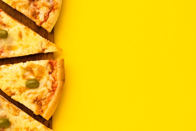Rebanada de pizza en placa de madera sobre fondo amarillo
