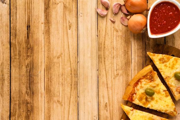 Rebanada de pizza y salsa con ingrediente crudo sobre superficie de madera