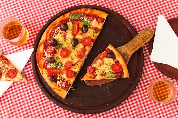 Rebanada de pizza servida en espátula sobre tablero circular de madera con fondo de mantel