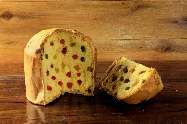 Rebanada de primer del panettone con la tabla de madera de las frutas confitadas. decoración navideña. frente v