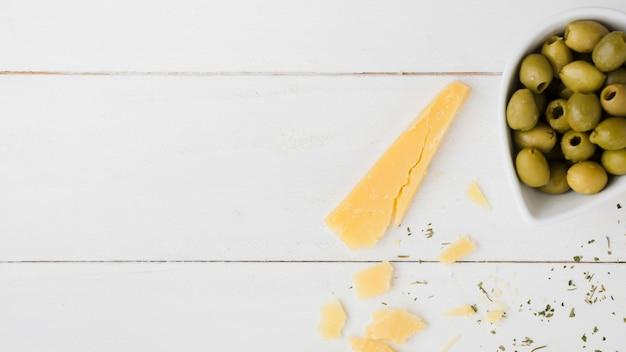 Rebanada de queso con aceitunas verdes en el recipiente en el escritorio de madera blanca