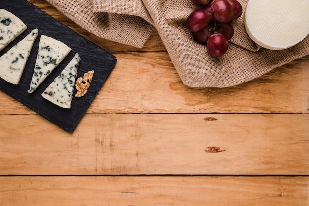 Rebanada de queso gorgonzola; nogal en piedra negra con uvas y queso manchego español sobre textura de arpillera