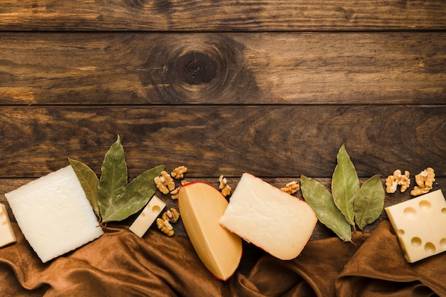 Rebanada de queso; hojas de laurel y nogal colocan en la parte inferior del fondo de madera con material textil de seda