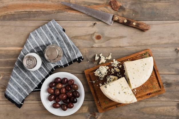 Rebanada de queso roquefort; aceitunas con salero y pimentero en mesa de madera