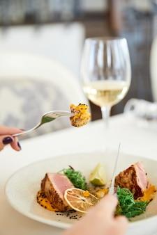 Rebanada de una sabrosa comida de atún con una copa de vino blanco en el restaurante.