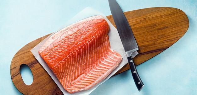Rebanada de salmón fresco en una tabla de cortar de madera con un cuchillo de chef sobre la mesa. receta de cocina.