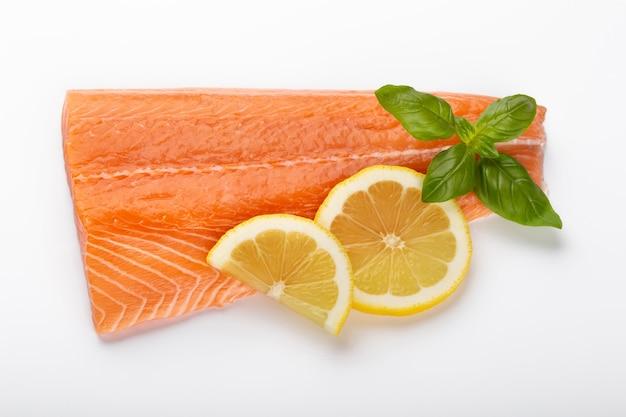 Rebanada de salmón rojo con limón, albahaca aislado en blanco.