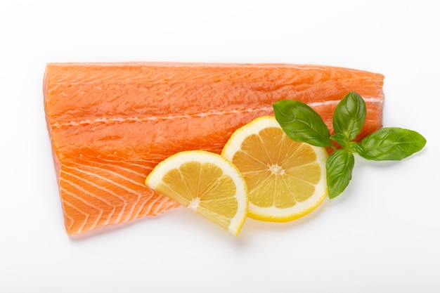 Rebanada de salmón rojo pescado con limón, albahaca aislado en blanco