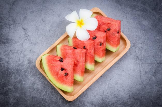 Rebanada de sandía fresca y flor blanca sobre negro, fruta tropical de sandía en bandeja de madera, enfoque selectivo
