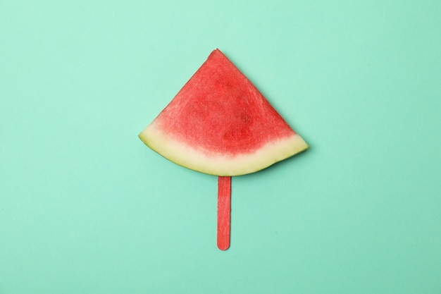 Rebanada de sandía en palito de helado en espacio de menta. fruta de verano