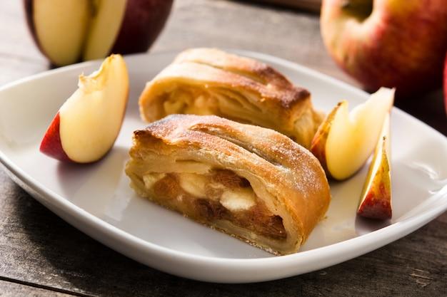 Rebanada de strudel de manzana casera tradicional en mesa de madera