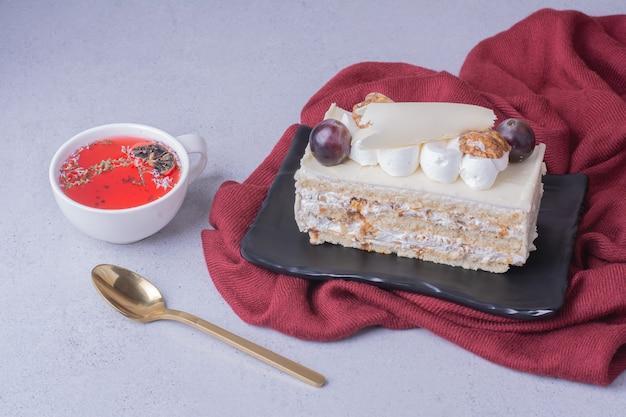 Una rebanada de tarta de coco con nueces y bayas servida con una taza de bebida roja