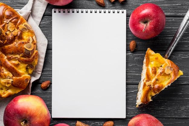 Rebanada de tarta de manzana y libreta de copia vacía