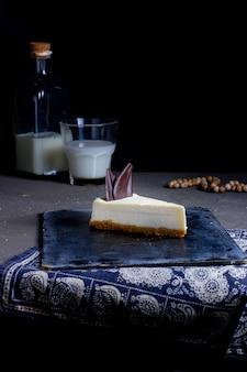 Rebanada de tarta de queso adornada con trozo de chocolate
