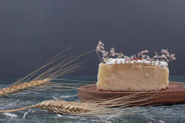 Rebanada de tarta de queso en placa de madera con trigo.