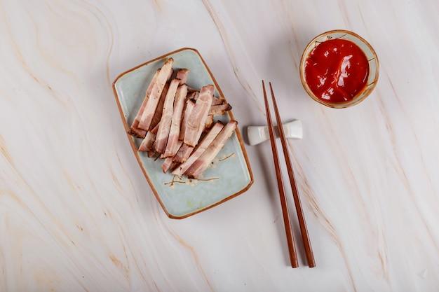 Rebanadas asiáticas de carne frita en un plato con salsa y palillos