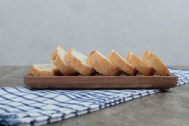 Rebanadas de baguette fresco en placa de madera con mantel. foto de alta calidad