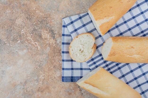 Rebanadas de baguette fresco sobre mantel rayado