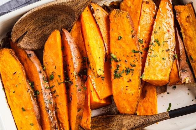 Rebanadas de batata al horno con especias en una fuente de horno. concepto de comida vegana saludable.