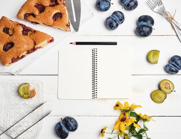 Rebanadas de bizcocho pastel de ciruela sobre una tabla de madera blanca y frutas frescas