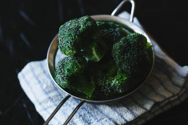 Rebanadas de brócoli en un colador sobre fondo negro.