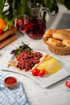 Rebanadas de carne de bbq a la parrilla, doner en lavash con ensalada verde, tomates y guarnición de arroz