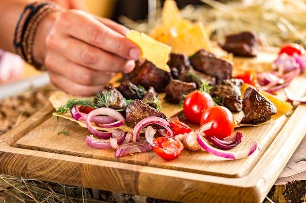 Rebanadas de carne frita con cebolla y tomates cherry en un fino pastel plano. la mano femenina toma un pedazo de pastel. colores horizontales y brillantes, espacio para texto.