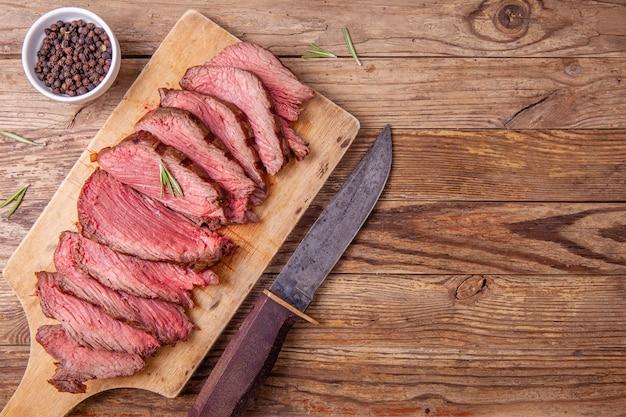Rebanadas de carne mediana de rosbif en tabla de cortar de madera y cuchillo de cazadores