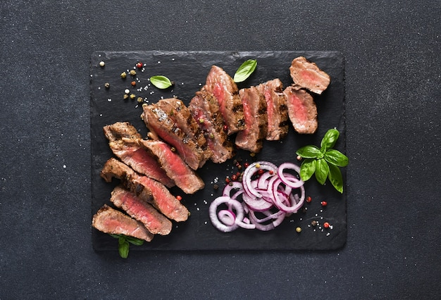Rebanadas de carne rara en una tabla de piedra con cebolla y albahaca. filete de ternera medio raro sobre fondo negro.