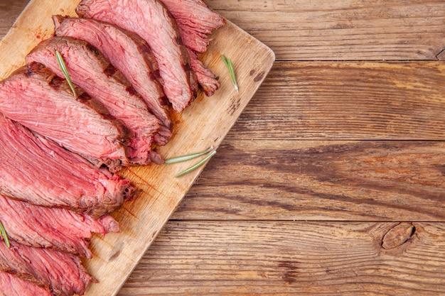 Rebanadas de carne de rosbif poco común en tabla de cortar de madera. copyspace