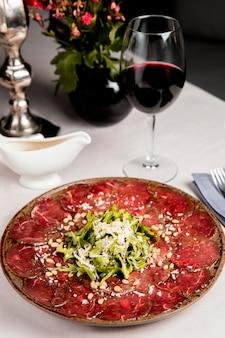 Rebanadas de carne con rúcula y queso rallado servidas con una copa de vino.