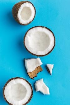 Rebanadas de cocos tropicales rotos en azul. vista superior