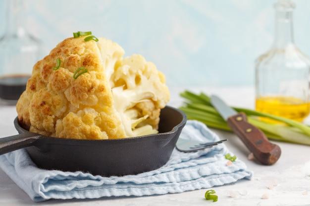 Rebanadas de coliflor entera al horno en una sartén de hierro fundido. concepto de comida vegana saludable.