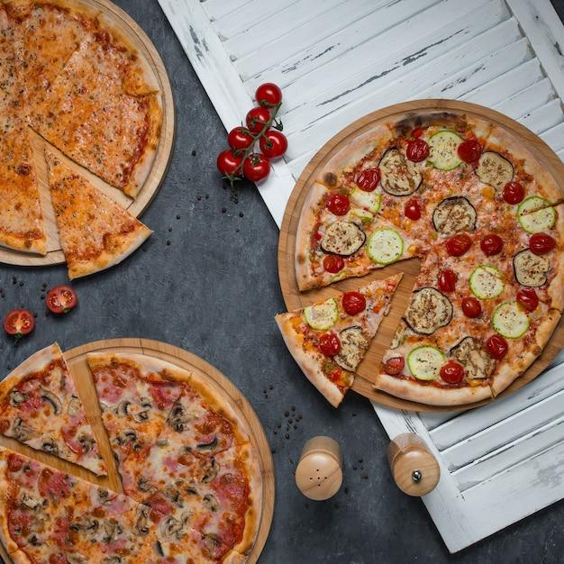 Rebanadas cortadas de tres variedades de pizzas.
