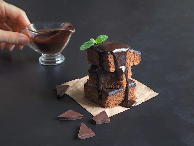 Rebanadas de delicioso brownie en una pila y se vierte con chocolate