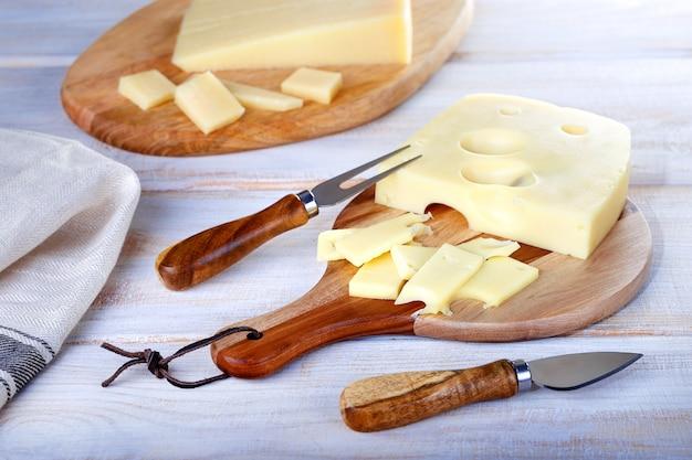 Rebanadas de delicioso queso parmesano y queso maasdam sobre tablas de madera.