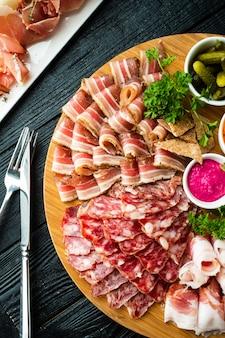 Rebanadas de diferentes tipos de salchichas y carnes ahumadas con salsa de rábano picante, encurtidos y verduras.