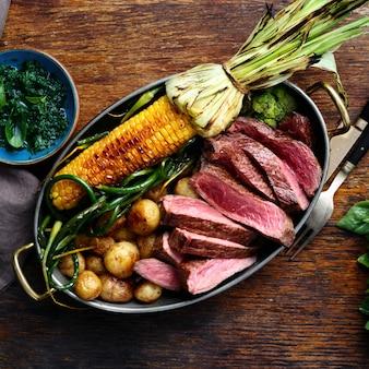 Rebanadas de filete de res en una sartén con vista superior de verduras