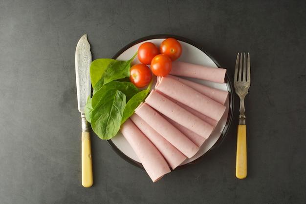 Rebanadas finas de jamón enrolladas en un plato con verduras frescas
