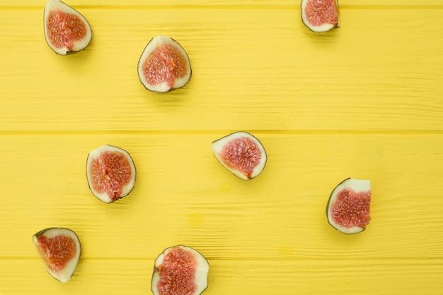 Rebanadas frescas de higos en fondo de madera amarillo. fruta para la salud. vista superior