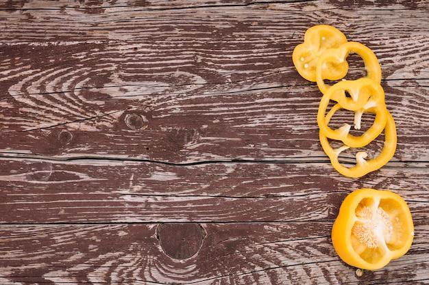 Rebanadas frescas orgánicas de paprika amarillo en el fondo texturizado resistido de madera