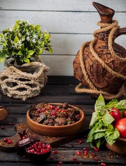 Rebanadas de kebab de cordero adornadas con granada y hierbas en una sartén de arcilla