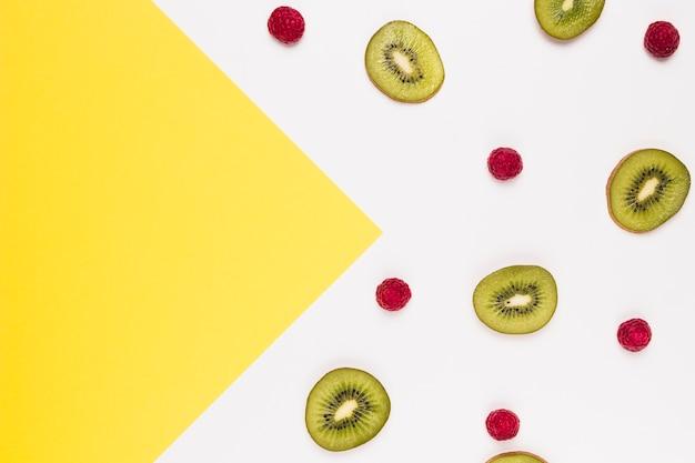 Rebanadas de kiwi y frambuesa sabrosos en fondo multicolor