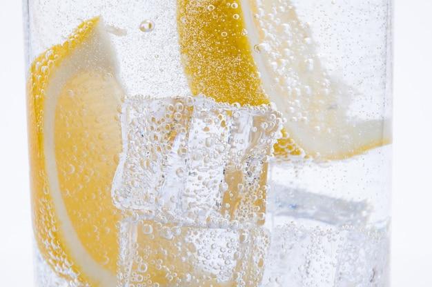 Rebanadas de limón amarillo jugoso fresco con hielo en agua.