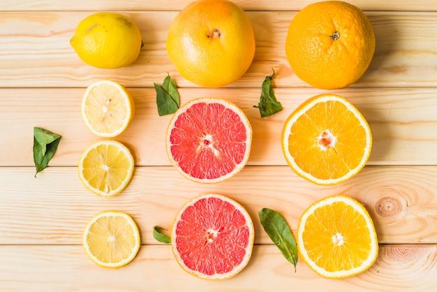 Rebanadas de limón; pomelo y naranja sobre fondo de madera
