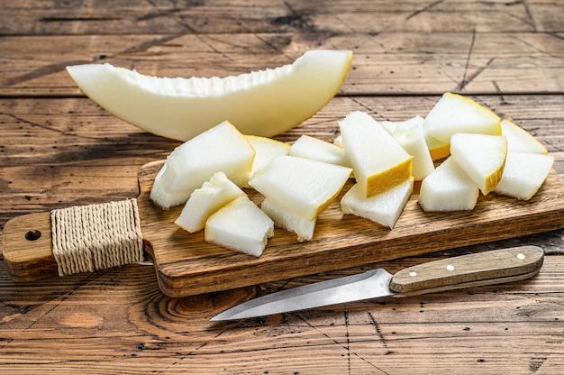 Rebanadas de melón amarillo en la tabla de cortar