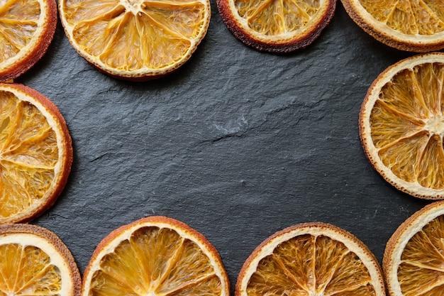 Rebanadas de naranja seca brillante sobre un fondo con textura de piedra, espacio de copia, plano, vista desde arriba, horizontal